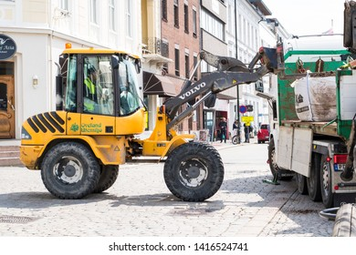 ARENDAL NORWAY - JULY 04, 2019 : Yellow Volvo tractor working in the Arendal city. Norway 2019.