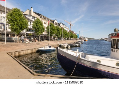 Arendal, Norway - june 5, 2018: Boats, buildings and people in Pollen, Arendal, on a sunny day. Blue sky and ocean.