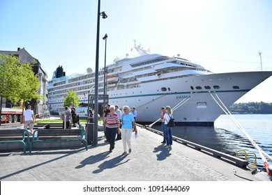 ARENDAL, NORWAY - MAY 15, 2018: A big tourist boat name's Amadea on the port, visiting Arendal City. Many tourist walking around and enjoy the center of city in Arendal, Norway.