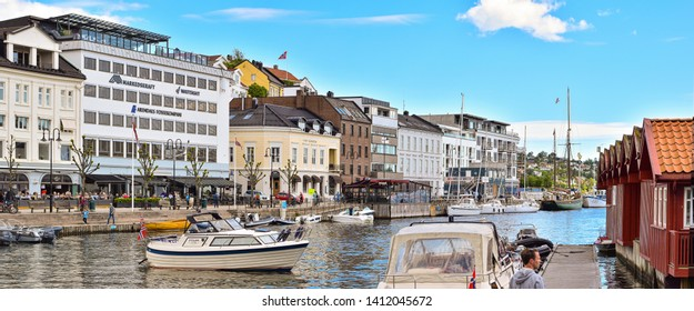 ARENDAL NORWAY - MAY 25, 2019 : Old Building and Tourist boat in Pollen harbour in Arendal, Norway