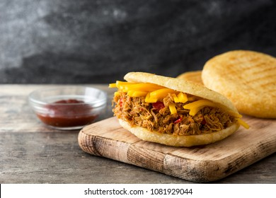 Arepa with shredded beef and cheese on wooden background. Venezuelan typical food