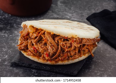 Arepa stuffed with shredded meat on a dark background. (Arepa con carne mechada)