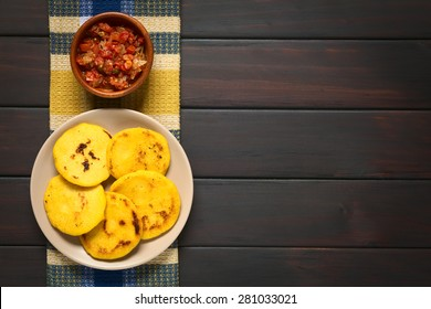 Arepas, fried cornmeal patties, with Colombian hogao sauce (tomato and onion cooked). Arepas are traditionally eaten in Colombia and Venezuela. Photographed on dark wood with natural light.