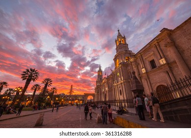 Arequipa, Peru - August 16, 2015: People roaming in Plaza de Armas in front of the Cathedral of Arequipa at dusk. Wide angle view from below with scenic colorful sky and clouds.