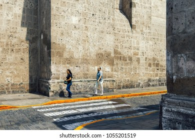 Arequipa, Peru - February 4, 2018: Daily Image. A man walks behind a woman next to the wall of the Convento de la Merced at the afternoon of Arequipa.