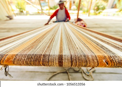 Arequipa, Peru - February 4, 2018: Macro of loom. A Peruvian woman weaves a loom in the courtyard of a workshop during the afternoon