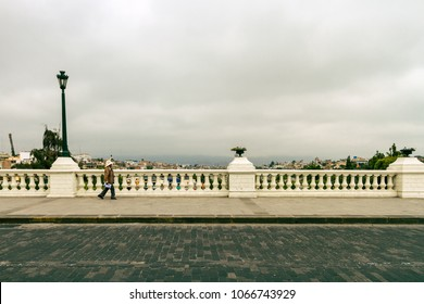 Arequipa, Peru - February 6, 2018: Daily image. An older woman walks by the sidewalks of the Grau Bridge in Arequipa in the direction of the Yanahuara neighborhood during a cloudy afternoon