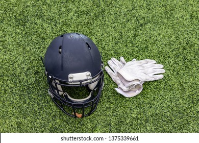 Arerial view of a football helmet and a pair of white gloves are laying on the grass