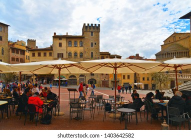AREZZO, ITALY 25.04.2019. Cityscape with Piazza Grande square in Arezzo with facade of old historical buildings and people relaxing on outdoor restauran tables against cloudy sky , Tuscany, Italy