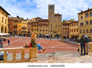 AREZZO, ITALY 25.04.2019. Cityscape with Piazza Grande square in Arezzo with facade of old historical buildings and young woman relaxing on stone fence against cloudy blue sky , Tuscany, Italy