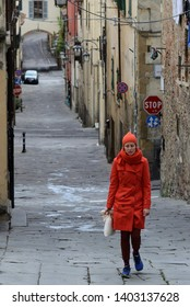 Arezzo, Italy, April 29, 2019:  lady with heavy red clothes strolls through the old streets of the historic center of Arezzo, in the cold spring