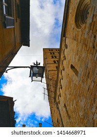 AREZZO, ITALY  Cityscape with lamp against cloudy blue sky in Arezzo with facade of old historical buildings and church , Tuscany, Italy