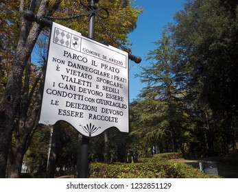 "AREZZO, ITALY - OCTOBER 14, 2018: Italian signpost with park rules: ""Do not damage the lawns. Do not litter the paths or damage the seats. Dogs must be on a leash. Pet waste must be picked up""."