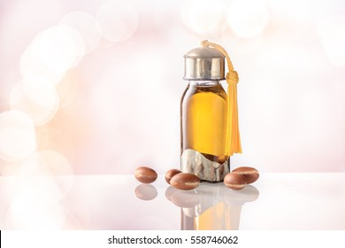 Argan oil and fruits on white with golden bokeh