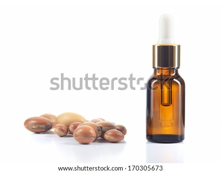 Argan oil and group of argan nuts isolated on white background. Body oil in brown bottle.