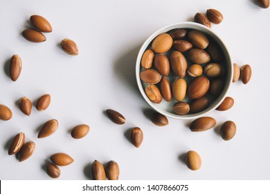 Argan seeds and nuts used for skin and healthcare on a white minimalist background