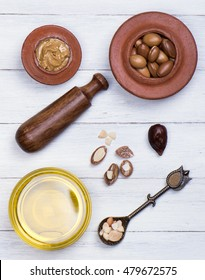 argan seeds and oil on white wood