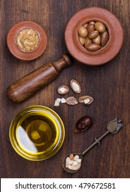 argan seeds and oil on wood
