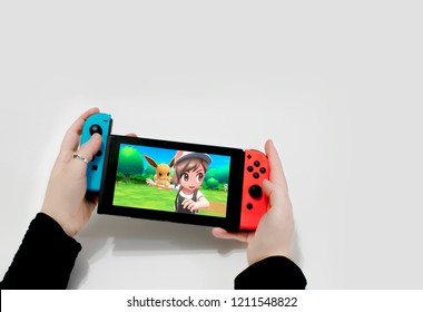 Argentina 20 of august 2018. young woman playing in nintendo switch, let's go eevee!, pokémon. Red and Blue joy con