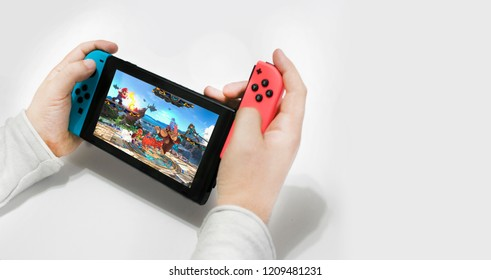 Argentina, 22 of August of 2018, young caucansian man playing super smash brothers on nintendo switch with white background.
