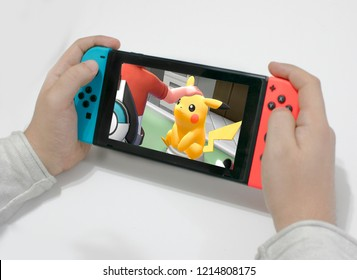 Argentina 28 of October 2018- caucasian young man playing pokémon let's go pikachu on a nintendo switch red and blue.