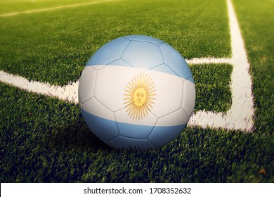 Argentina flag on ball at corner kick position, soccer field background. National football theme on green grass.