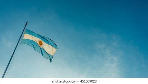 Argentina flag waving on a sunny day against blue sky