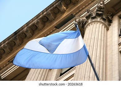 Argentina flag waving in the wind with old building in background.