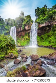 Argentina, Iguazu Falls. Two powerful fairy waterfalls falls into a small quiet pond. The concept of extreme and ecological tourism. Hot tropical sun illuminates the rumbling waterfalls