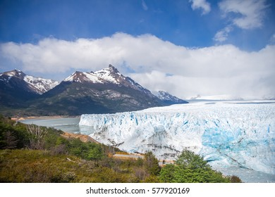 Argentina, Patagonia. Beautiful landscape with Perito Moreno glacier, Lago Argentino (Argentinian lake) snow covered mountains and a small forest. Good weather, blue sky and some clouds.
