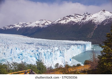 Argentina, Patagonia. Beautiful landscape with Perito Moreno glacier, Lago Argentino (Argentinian lake) snow crapped mountains and a small forest. Good weather, blue sky and some clouds.