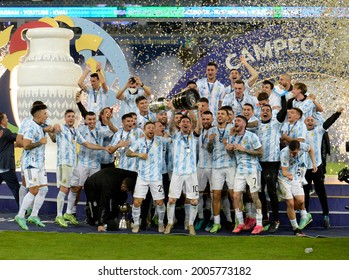 Argentina's Lionel Messi holds the trophy as he celebrates with teammates after beating 1-0 Brazil in the Copa America final soccer match at the Maracana stadium in Rio de Janeiro, Brazil 10 Jul 2021