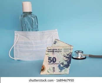 argentine banknote of fifty pesos, mask, bottle with gel alcohol and stethoscope on blue background