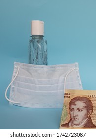 argentine banknote of ten pesos, face mask, bottle with gel alcohol and blue background