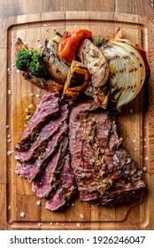 Argentine cut of meat called Vacio with chorizos and chimichurri.