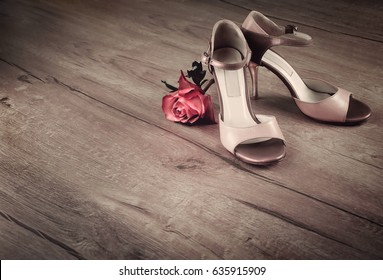 Argentine tango shoes with a rose on wooden floor, space for your text