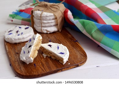 argentinean alfajores filled with dulce de leche and coated with a white meringue, decorated with dried flowers cornflower on a wooden chopping board, on white a rustic table