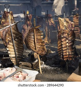 Argentinean asado (BBQ) of rack of ribs that are being roasted on crosses (estaca) or stakes over firewood