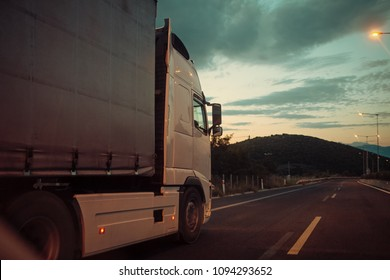 argo van, truck, kamion transports goods or items between countries. International transportation concept. Camion, van rides along the road in evening, rear view.