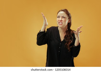 Argue, arguing concept. Beautiful female half-length portrait isolated on gold studio backgroud. Young emotional surprised woman looking at camera.Human emotions, facial expression concept.