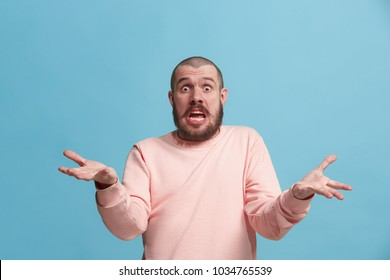 Argue, arguing concept. Beautiful male half-length portrait isolated on blue studio backgroud. Young emotional surprised man looking at camera. Human emotions, facial expression concept. Front view