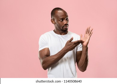 Argue, arguing concept. Beautiful male half-length portrait isolated on pink studio backgroud. Young emotional surprised man looking at camera. Human emotions, facial expression concept. Front view