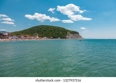 Arhipo-Osiovka, Russia - July 5, 2018: Exotic water landscape with clouds on horizon. Natural tropical water paradise. People relax on the beach. Travel tropical island resort.