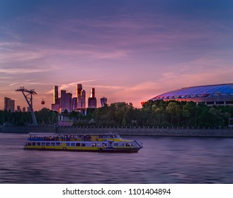 The aria of the stadium in Moscow with Moscva river and floating bout and with pink sky and clouds on the background.