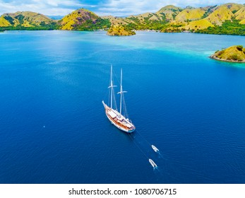 Arial view of beautiful scenery at Flores island with tourist yatch, turqouise and dark blue sea.