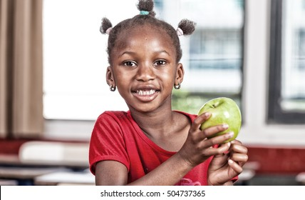 Arican girl at primary school holding green apple in classroom.