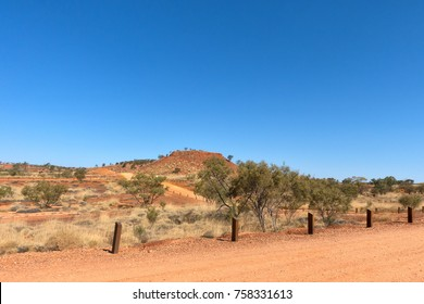 Arid landscape and wooden bollards at Lark Quarry, the location of the dinosaur stampede, in rural Queensland, Australia