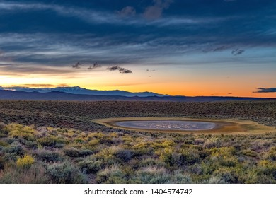 An arid Owens Valley with colorful fall sagebrush and grasses in orange sunrise light across horizon line with snow capped mountains and in foreground a large waterhole reflects the sky.