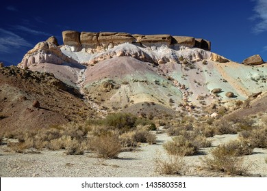 Arid vegetation leads to the 'Seven Colored Hill' next to a mountain road above the Argentinian village of Uspallata. This extraordinary hill has colors of he rainbow and a flat summit.