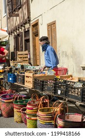 Ariege, France, 2015. Man wearing French berry cap at traditional French market stall selling vegetables and eggs and woven baskets, with old timbered building in  the background.